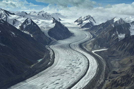 aerial photo of a glacier between mountains in alaska
