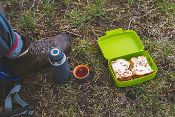 Shoe of hiker with thermos and lunch box in grass. Top view.