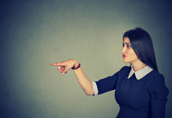 Displeased woman pointing finger at someone