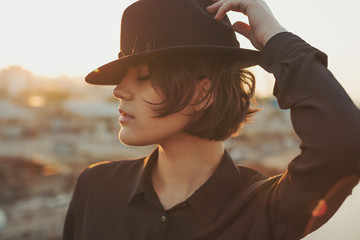 City style young woman with hat. Close up portrait. Urban sunset background. Dreaming mood.