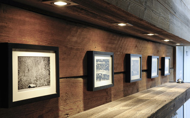 Picture frames and old pictures on a wooden wall in an renovated swiss chalet