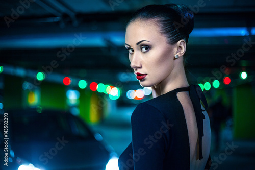 2846ad646e7 Young beautiful stylish girl walking and posing in short black dress in city