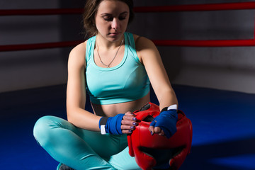 Athletic female boxer sitting and holding helmet