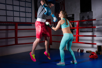 Athletic young woman in sportswear and in boxing gloves training with her couch