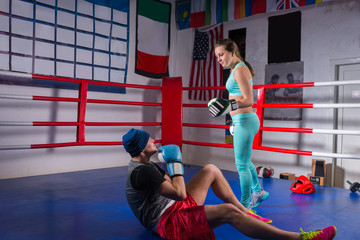 Sporty woman in sportswear and in boxing gloves training with her couch