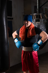 Young male boxer with a towel around his neck in a hat and boxing gloves  in a gym