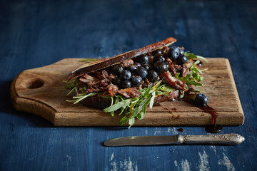 closed sandwich with roasted bacon, blueberries and arugula
