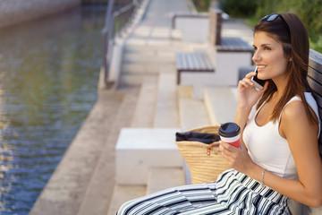 frau sitzt draußen in der stadt und telefoniert