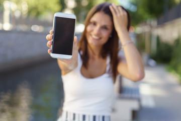 lächelnde frau sitzt in der stadt und zeigt ihr handy-display