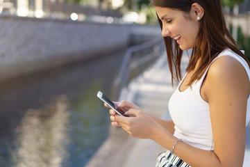 frau sitzt draußen in der stadt und schaut lachend auf ihr mobiltelefon