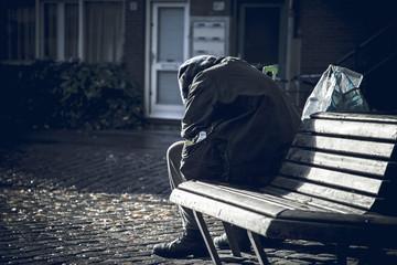 Einsamer Mann sitzt traurig auf einer Bank.
