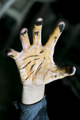 Human hand painted like tiger claws.