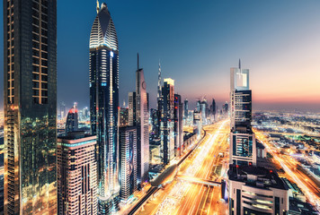 Spectacular nighttime skyline of Dubai, UAE.  Futuristic architecture of a big city at night. View over the famous highway with illuminated skyscrapers. Colourful travel background.