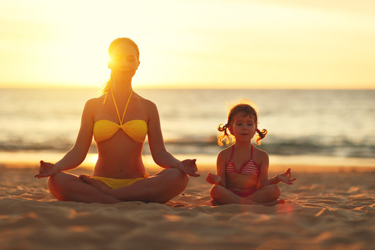 Happy family mother and child doing yoga, meditate in lotus position on beach .