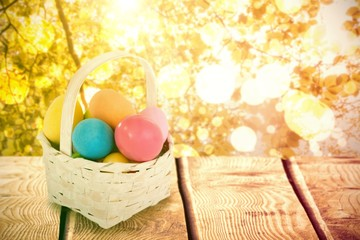 Composite image of mulit colored easter eggs in wicker basket