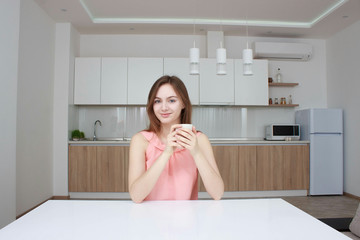 Smiling woman which sitting on kitchen with cup of coffee and looking at camera