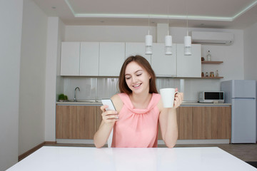 Beautiful girl in home using smartphone, drinking tea and smiling in kitchen