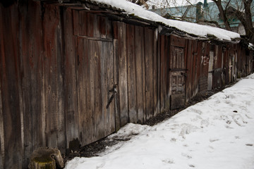 Old wooden shed of rough boards in winter with snow on the roof