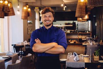 Cheerful waiter in modern restaurant