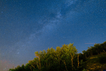 The starry sky and the Milky Way over the mountains and the forest.