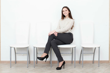Attractive girl sitting on white modern chair and relax at home