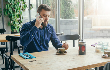 Young bearded businessman in blue shirt is sitting at wooden table near window in restaurant and talking on cell phone.