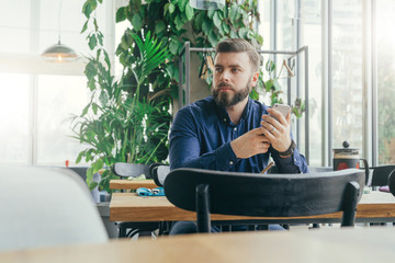 Young bearded attractive businessman in blue shirt is sitting at wooden table near window in restaurant