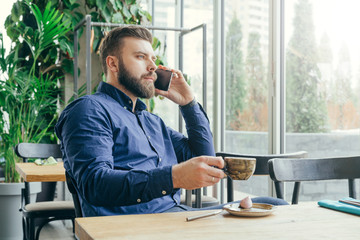 Side view.Young bearded attractive businessman in blue shirt is sitting at wooden table near window in restaurant