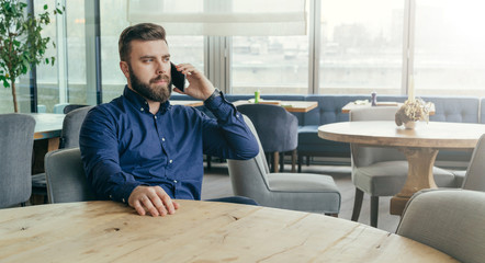 Bearded attractive businessman in blue shirt is sitting at wooden round table in restaurant and talking on cell phone.