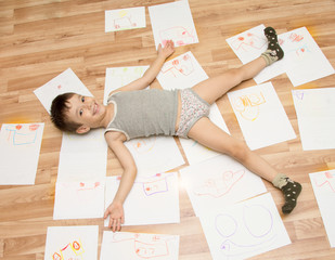 The child lies on the floor, and around the drawings