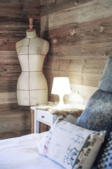 Cosy bedroom in an old wooden chalet with nightstand, fur, couturier's bust and cushions
