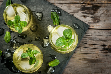 Traditional Spanish alcoholic drink, Rebujito cocktail - white wine, carbonated water (soda), mint, lemon juice. On a rustic wooden table, three glasses. Copy space