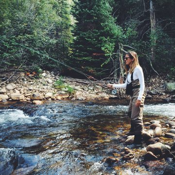 Young woman fly fishing along a Colorado stream