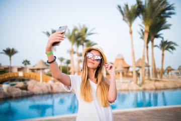 Close-up selfie-portrait of attractive girl with long hair standing near pool wears in sunglasses and hat smiling to the camera.