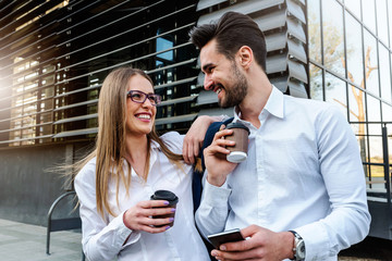 Smiling business couple outdoors in the street taking a coffee break