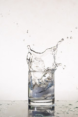 iced splashing water from glass on white background