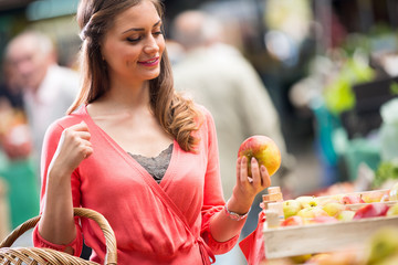 woman smiling with apples at market store.