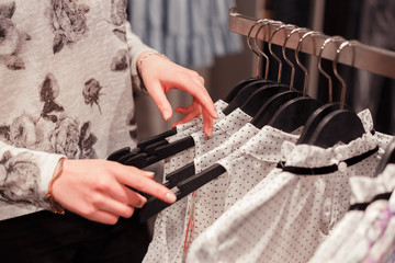 Close up woman hands on clothes hangers in a store buying clothes.Shopping.Woman decides what she is going to try on