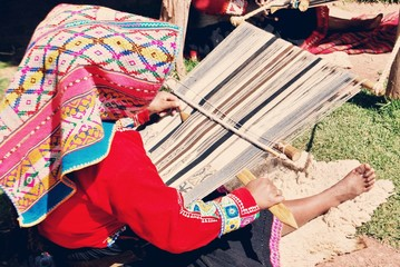 Peruvian woman sitting and weaving colorful textiles