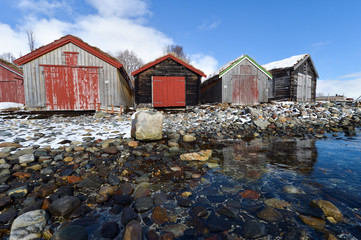 Traditional red wooden norwegian cabins with ground on the roof