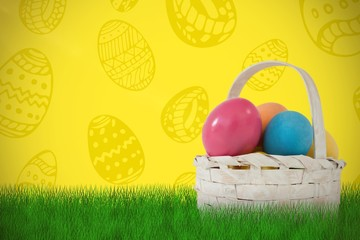 Composite image of easter eggs in wicker basket