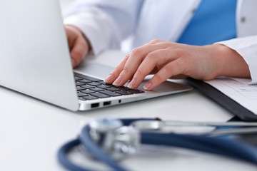 Close up of unknown female doctor typing on laptop computer while sitting  at the table. Medical staff, compulsory work concept