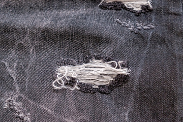 Destroyed torn black denim background. Trace on denim ripped jeans. Close up at the threads hole on black jeans. Selective focus