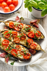Griled eggplants with cheese, cherry tomatoes and basil on white plate