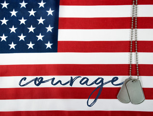 word courage and military dog tags on American flag