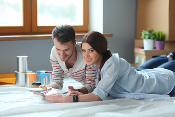 Couple choosing paint colour from swatch for new home lying on wooden floor