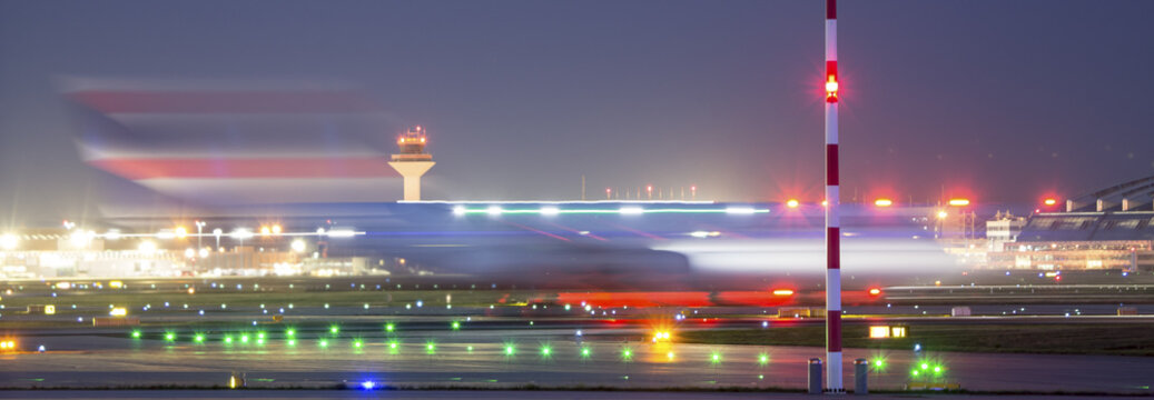 airplane starting speed blur at an airport at night
