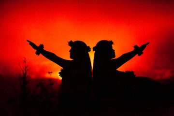 Profile of Hawaiian women hula dancing in front of volcano