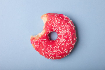 one bite tasty donut with pink glaze isolated on blue background