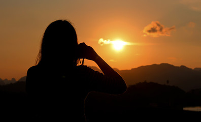 Asia woman photographer silhouette handing camera at sunset background.